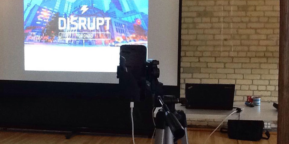A photo of my tripod and iPhone set up in front of a slideshow screen